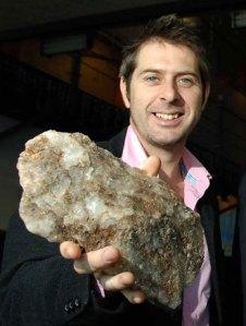Dr Iain Stewart holding a rock